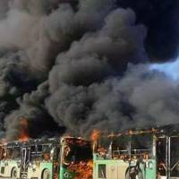 In this photo released by the Syrian official news agency SANA, smoke rises in green government buses, in Idlib province, Syria, Sunday. Activists said, militants have burned at least five buses assigned to evacuate wounded and sick people from two villages in northern Syria. The incident could scuttle a wider deal that encompasses the evacuation of thousands of trapped rebel fighters and civilians from the last opposition foothold in east Aleppo. | SANA VIA AP