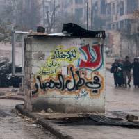 People carry their belongings as they flee deeper into the remaining rebel-held areas of Aleppo Tuesday. The Arabic words read, 'No to monopolizing commodities and raising prices under the siege.' | REUTERS