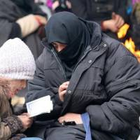A woman sits with her child reading the Quran while waiting to be evacuated with others from a rebel-held sector of eastern Aleppo, Syria, on Saturday. | REUTERS