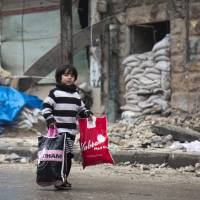 A Syrian boy is seen among other civilains leaving a rebel-held area of Aleppo toward the government-held side on Tuesday during an operation by Syrian government forces to retake the embattled city. | AFP-JIJI