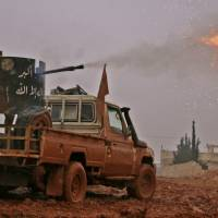 Syrian opposition fighters fire toward positions held by Islamic State (IS) group jihadis in al-Bab on the northeastern outskirts of the northern embattled city of Aleppo on Tuesday. | AFP-JIJI