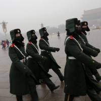 Paramilitary policemen leave after a flag-raising ceremony amid heavy smog in Beijing's Tiananmen Square in December 2015. | REUTERS