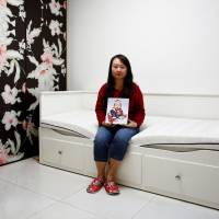 Dai Xiaolei holds a picture of her son in the bedroom she made for him in her former apartment in Beijing on Sept. 19. | REUTERS