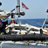 Unmanned underwater vehicle (UUV) operators assigned to the U.S. Navy's 5th Fleet launch one of the drone vessels during operations in January 2013. | COMMANDER, TASK GROUP (CTG) 56