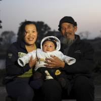 A Chinese couple pose with their son, their only child, in December 2013, before China eased family planning restrictions to allow couples to have two children. | REUTERS