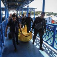 Police carry a body bag containing debris and belongings recovered from an aircraft carrying 13 police people that went missing on Saturday, in Batam, Riau Islands, Indonesia, Sunday. | ANTARA FOTO /M N KANWA /VIA REUTERS