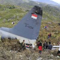 Rescuers collect personal belongings of the victims of an Indonesian Air Force plane that crashed in the mountainous area in Wamena, Papua province, Indonesia, Sunday. The Hercules C-130 transport plane crashed in bad weather in the easternmost province, killing all on board. | AP