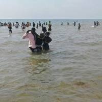 People help a man ashore from Lake Albert on Monday in Buliisa, after at least 30 Ugandan members of a village football team and their fans drowned when their boat capsized on Lake Albert during a party. Police officers working with local fishermen managed to rescue 15 of the revellers, who were heading from the village of Kaweibanda in the western Buliisa District to watch a friendly Christmas Day match in Hoima District, Rutagira said. | AFP-JIJI