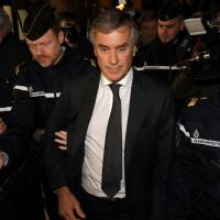Former French budget minister Jerome Cahuzac, who resigned in 2013 after he admitted to having a Swiss bank account, is surrounded by French gendarmes as he leaves after the verdict in his tax fraud trial in Paris on Thursday. | REUTERS