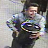 An unidentified man is shown in this image from surveillance video carrying an 86-pound pail of gold flakes valued at $1.6 million off an armored truck two months ago in Manhattan. | COURTESY OF NYPD / HANDOUT VIA REUTERS