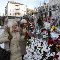 Women place flowers for the 92 victims of the Dec. 25 Russian air crash over the Black Sea in front of the Russian Embassy building in Kiev on Monday. | AP