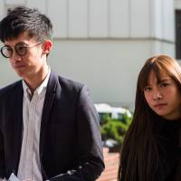 Pro-independence lawmakers Baggio Leung (left) and Yau Wai-ching arrive to speak to reporters outside the High Court in Hong Kong on Wednesday. | AFP-JIJI