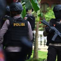 Indonesian police officers stand outside a home following a gunfight in which three suspected militants were killed in South Tangerang, Banten province near Jakarta Wednesday. | ANTARA FOTO / MUHAMMAD IQBA / VIA REUTERS