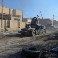 Military vehicles of the Iraqi security forces are seen during a battle with Islamic State militants in Mosul Sunday. | REUTERS