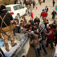 Iraqi soldiers distribute water to children outside a distribution point run by United Nations agencies at Zahra district, east of Mosul, Iraq, Thursday.   REUTERS