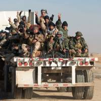 Shiite fighters from the Hashed al-Shaabi (Popular Mobilization units) flash the sign for victory as they sit in the back of a truck near the village of Ayn Nasir, south of Mosul, on Sunday during the ongoing operation against Islamic State (IS) group jihadis. | AFP-JIJI