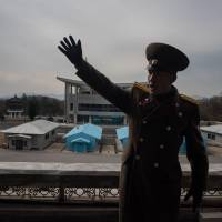 A Korean People's Army soldier gestures before the joint security area and Demilitarized Zone (DMZ) separating North and South Korea in Panmunjom, near Kaesong, on Wednesday. | AFP-JIJI
