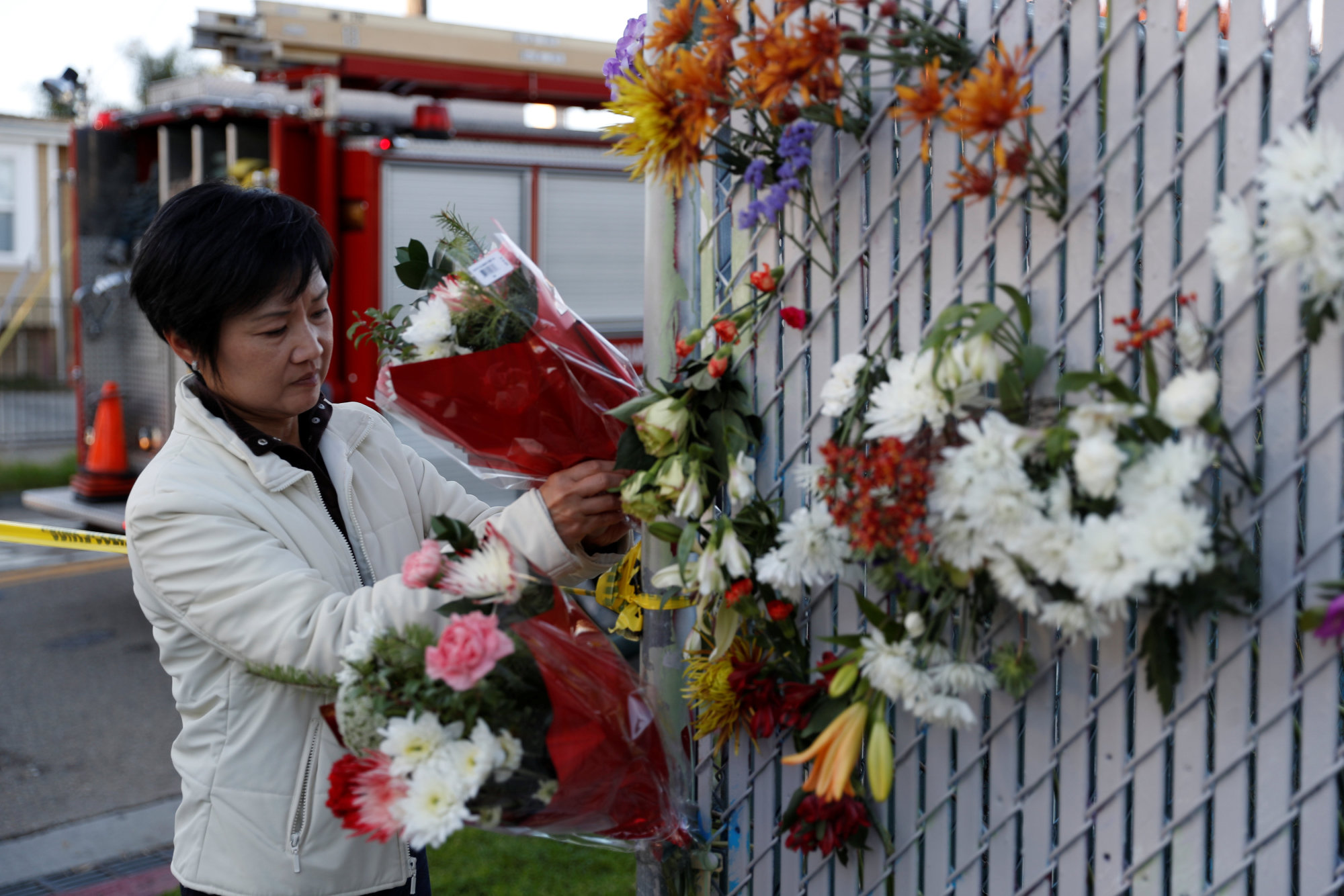 A woman places flowers at a makeshift memorial on Saturday near the scene of a deadly fire in Oakland, California.   REUTERS