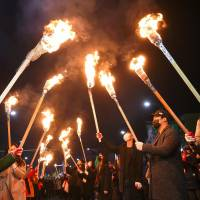 South Korean protesters carry torches as they march toward the presidential Blue House during a rally against President Park Geun-hye in central Seoul on Sunday.   AFP-JIJI