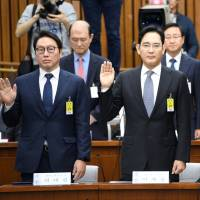 SK Group chairman Chey Tae-won (left), Samsung Group heir-apparent Lee Jae-yong (center) and Lotte Group Chairman Shin Dong-bin take an oath during a parliamentary probe into a scandal engulfing the administration of South Korean President Park Geun-hye at the National Assembly in Seoul on Tuesday. | REUTERS