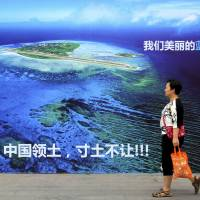 A billboard in Weifang, China, in July shows an island in the South China Sea and reads in part, 'Our beautiful motherland, we won't let go of an inch.' | AP