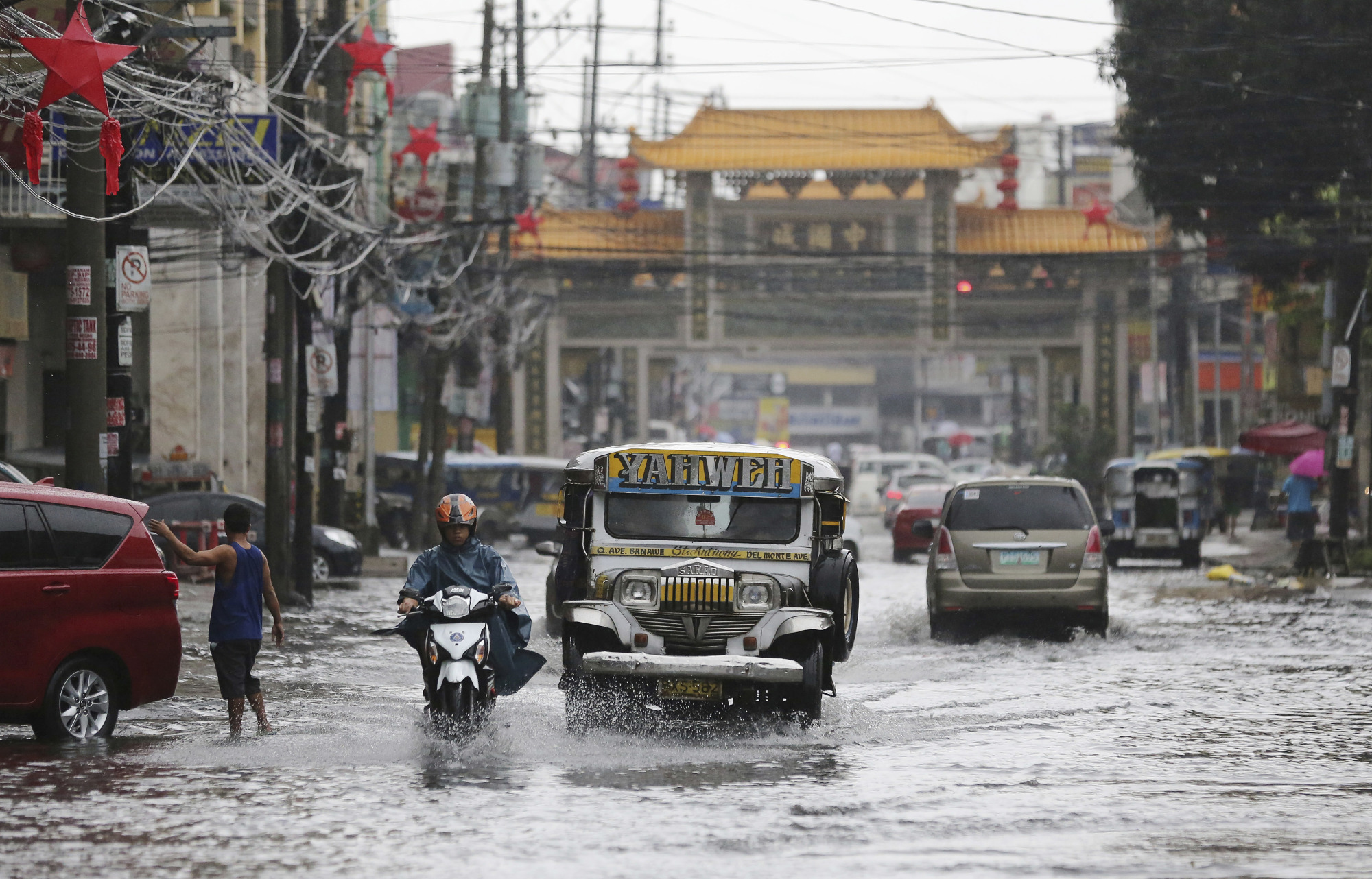 A jeepney navigates a flooded street in Quezon City, north of Manila, following heavy rain after Typhoon Nock-Ten hit the Philippines on Monday. | AP