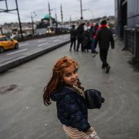 A Syrian refugee girl begs on the Galata Bridge on a rainy Wednesday in Istanbul. | AFP-JIJI