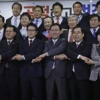 Saenuri Party lawmakers hold a news conference at the National Assembly in Seoul on Tuesday to announce they are leaving the ruling party over the corruption scandal involving impeached President Park Geun-hye.   AP