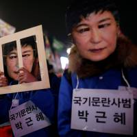 People march during a protest calling for South Korean President Park Geun-hye to step down in central Seoul on Wednesday. The signs read: 'Offender disturbing order of nation, Park Geun-hye.' | REUTERS