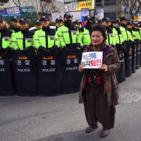 A South Korean protester holds a banner reading, 'Step down Park Geun-hye!' during a protest outside the ruling Saenuri Party's headquarters in Seoul on Saturday. | AFP-JIJI