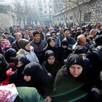 Civilians wait outside a military police center to visit relatives who were evacuated from the eastern districts of Aleppo, Syria, and are being prepared to begin their military service Sunday. | REUTERS