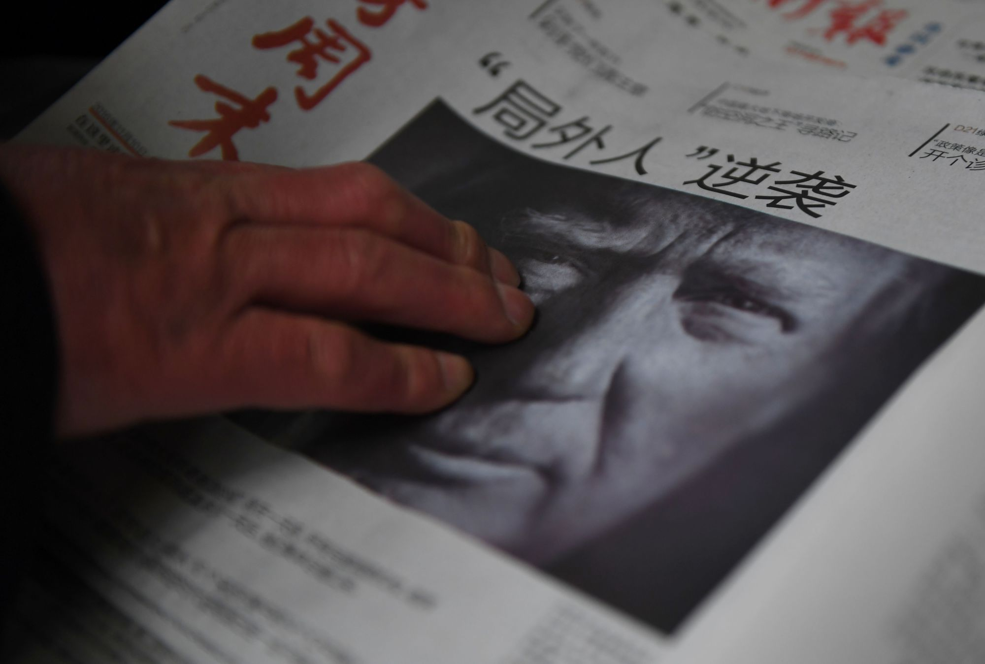 A man buys a newspaper featuring U.S. President-elect Donald Trump at a newsstand in Beijing on Nov. 10. | AFP-JIJI