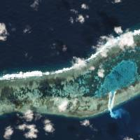 Sand can be seen spilling from a newly dredged channel in this view of Vietnamese-held Ladd Reef, in the Spratly Island group in the South China Sea, Nov. 30in this Planet Labs handout photo received by Reuters on Tuesday. | TREVOR HAMMOND / PLANET LABS / HANDOUT VIA REUTERS