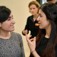 Nadia Murad, U.N. Goodwill Ambassador for the Dignity of Survivors of Human Trafficking, gestures to Lamiya Aji Bashar after both received the 2016 the European Parliament's prestigious Sakharov human rights prize Thursdayk at the Landtag state pariament of Baden-Wuerttemberg in Stuttgart, Germany. | FRANZISKA KRAUFMANN / DPA / AFP-JIJI