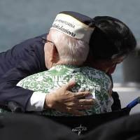 Japanese Prime Minister Shinzo Abe embraces a World War II Pearl Harbor survivor after he and U.S. President Barack Obama spoke on Kilo Pier, overlooking the USS Arizona Memorial, at Joint Base Pearl Harbor-Hickam Tuesday. Abe and Obama made a historic pilgrimage Tuesday to the site where the devastating surprise attack sent America marching into World War II. | AP