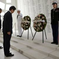 Prime Minister Shinzo Abe (center) and U.S. President Barack Obama bow their heads during a wreath-laying ceremony aboard the USS Arizona Memorial at Pearl Harbor, Hawaii, Tuesday. | REUTERS