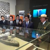 Prime Minister Shinzo Abe (center) looks at a model of the USS Arizona Wednesday at the Pearl Harbor Visitors Center along with Defense Minister Tomomi Inada and Foreign Minister Fumio Kishida. | ERIC JOHNSTON