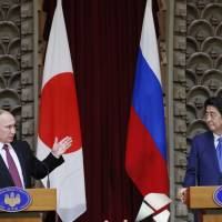 Russian President Vladimir Putin speaks as Prime Minister Shinzo Abe looks on during a news conference in Tokyo on Friday. Russia and Japan agreed to hold talks on the joint economic development of four islands at the center of a territorial dispute. | AP