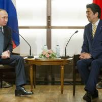 Russian President Vladimir Putin chats with Prime Minister Shinzo Abe at the start of their two-day summit in Nagato, Yamaguchi Prefecture, on Thursday. | AP