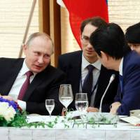 Russian President Vladimir Putin (left) confers with Prime Minister Shinzo Abe during a working lunch in Tokyo on Friday. | AFP-JIJI