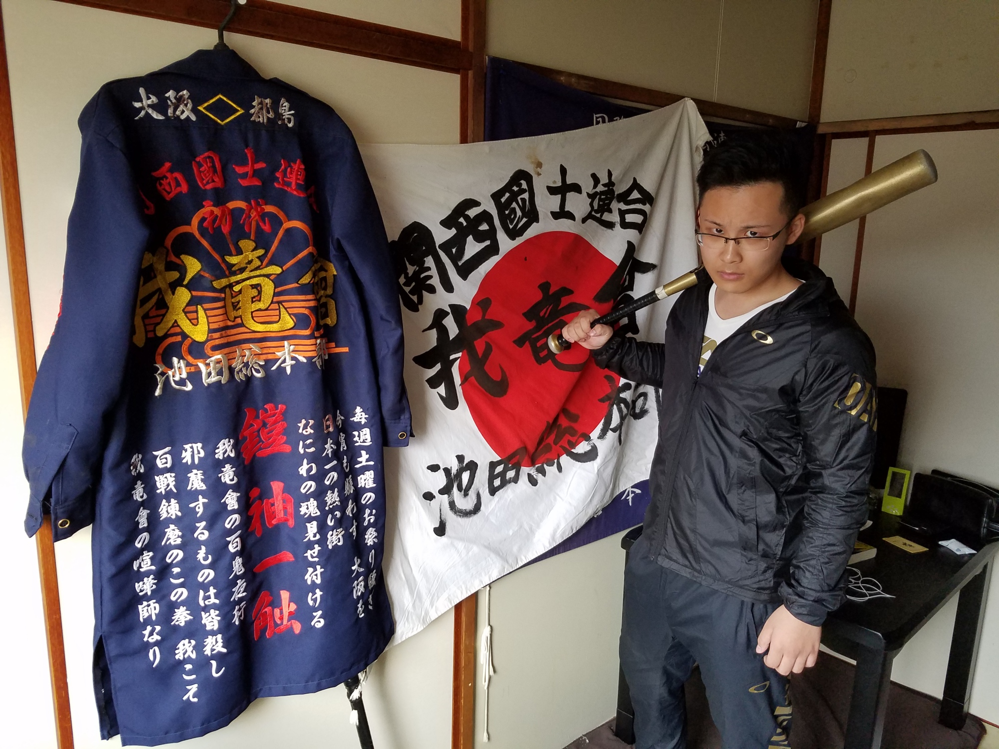 Former 'bosozoku' biker Shotaro Nagasawa, 20, poses at his home in Osaka on Nov. 6. Embroidered on his 'tokkofuku' fighting jacket is a four-letter slogan that reads 'gaishu isshoku,' meaning 'vanquish your enemy with a single blow.' | TOMOHIRO OSAKI