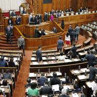 Upper House lawmakers vote on a pension reform bill during the chamber's plenary session Wednesday. They later approved a controversial casino bill. | KYODO