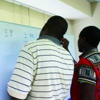 Two asylum seekers from Africa take a Japanese lesson in Tokyo in July. | JAPAN ASSOCIATION FOR REFUGEES
