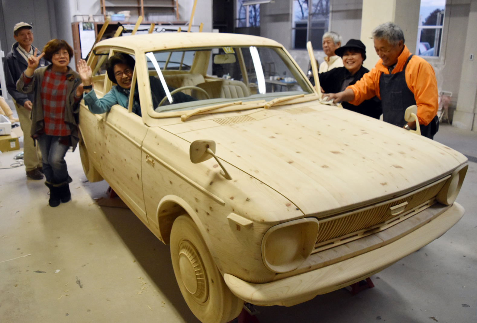Members of a volunteer group pose around a life-sized wooden replica of a first-generation Toyota Corolla on Dec. 8 in Toyota, Aichi Prefecture.   CHUNICHI SHIMBUN