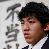 Utinan Won, a 16-year-old high school student living in Japan without a visa, attends a news conference in Tokyo on Tuesday. The characters on the wall are part of a banner that reads, 'Unjust ruling.' | REUTERS