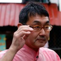 Katsuyuki Kawai, a special adviser to Prime Minister Shinzo Abe, tours a government-run drug rehabilitation center in Taguig in the Philippines on Monday. | REUTERS