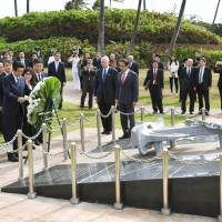 Prime Minister Shinzo Abe lays flowers as other officials look on at the Ehime Maru Memorial in Honolulu on Monday. | KYODO