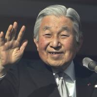 Emperor Akihito waves to well-wishers on Dec. 23, his 83rd birthday, from behind bullet-proof glass enclosing the balcony of the Imperial Palace in Tokyo. | AP