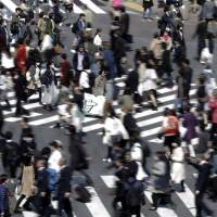 Pedestrians cross an intersection in Tokyo. The government on Tuesday unveiled a draft guideline for a system of 'equal pay for equal work' regardless of employment status. | BLOOMBERG
