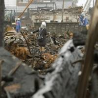 A woman carrying a shovel searches for her belongings in a fire-ravaged neighborhood of Itoigawa, Niigata Prefecture, on Saturday. | KYODO